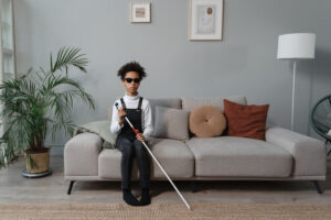 woman with white cane sitting on the couch